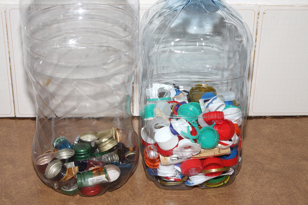 Plastic bottle caps, straps and other small items are placed inside an empty water bottle.